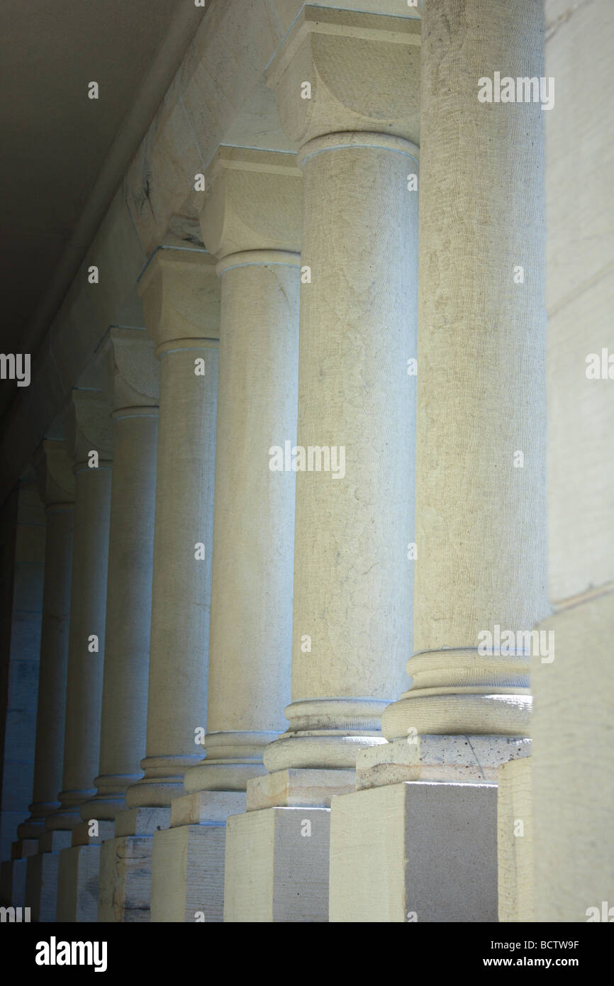 Arcade of white cylindrical columns supporting roof - Stock Image