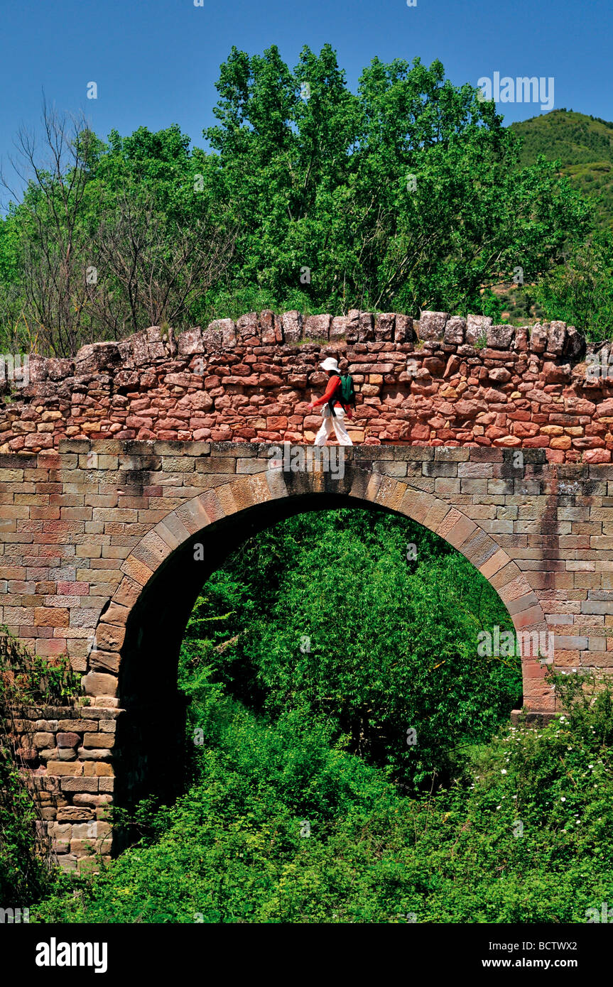 Spain, St. James Way: Pilgrim at the bridge of Cirauqui along the legendary Camino Frances - Stock Image