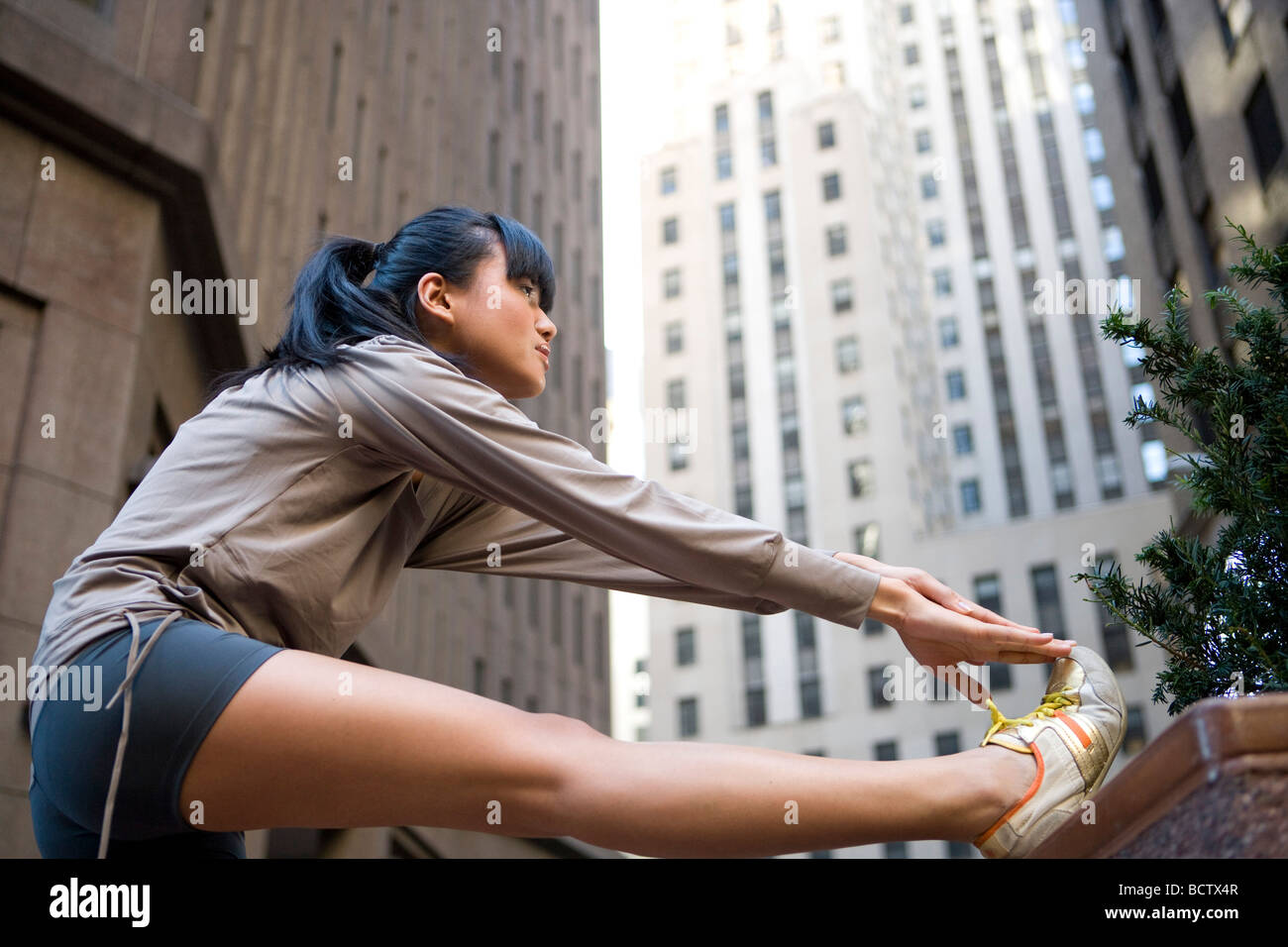 Side profile of a young woman touching her toes - Stock Image