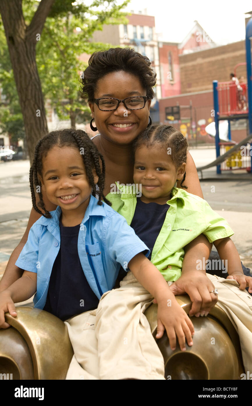 Single mother with her two children at a playground in New York City - Stock Image
