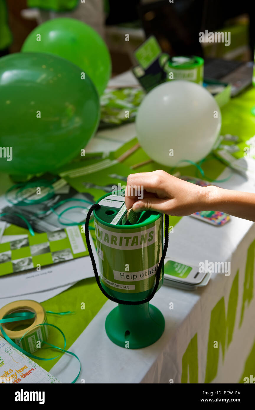 A person donating a pound coin to the charity The Samaritans. - Stock Image