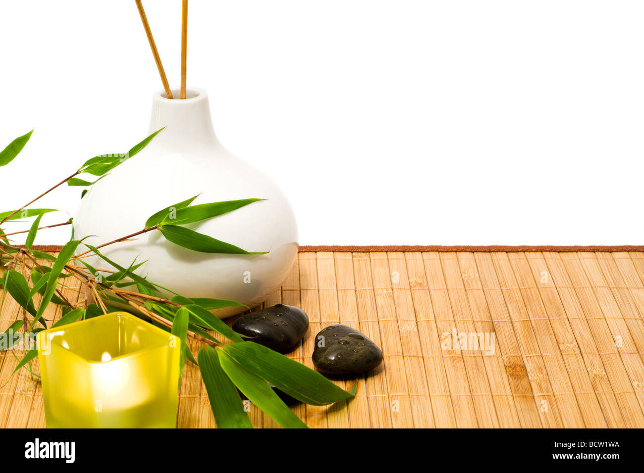 spa and wellness still-life with bamboo branch, candle, stones, vase with incense sticks, cutout - Stock Image