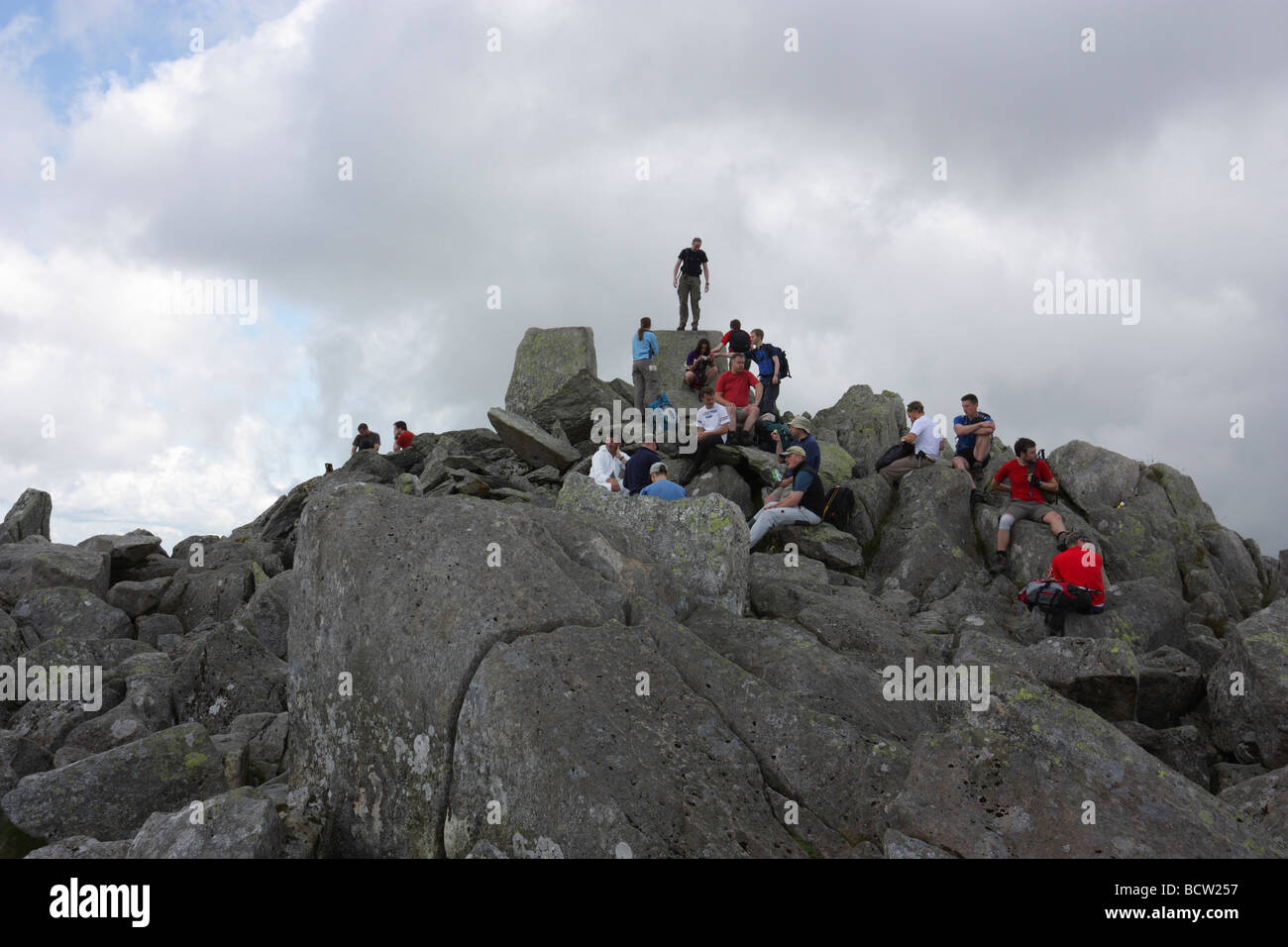Hill walkers and scramblers on the summit of Tryfan, a peak in Snowdonia, North Wales - Stock Image