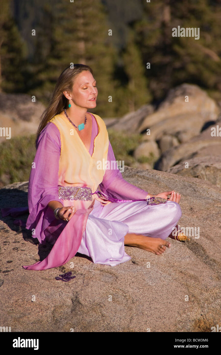 Mature woman in flowing robes meditating on a rock - Stock Image