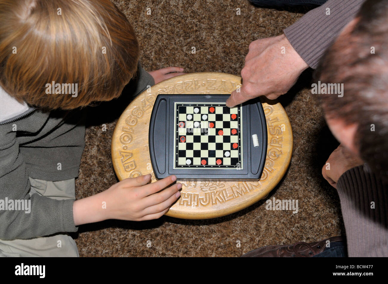 Looking down on a father and son playing a game of drafts. - Stock Image