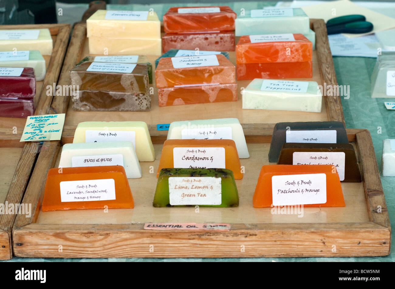 Blocks of 'vegetable glycerine' soaps on a market stall  tray - Stock Image