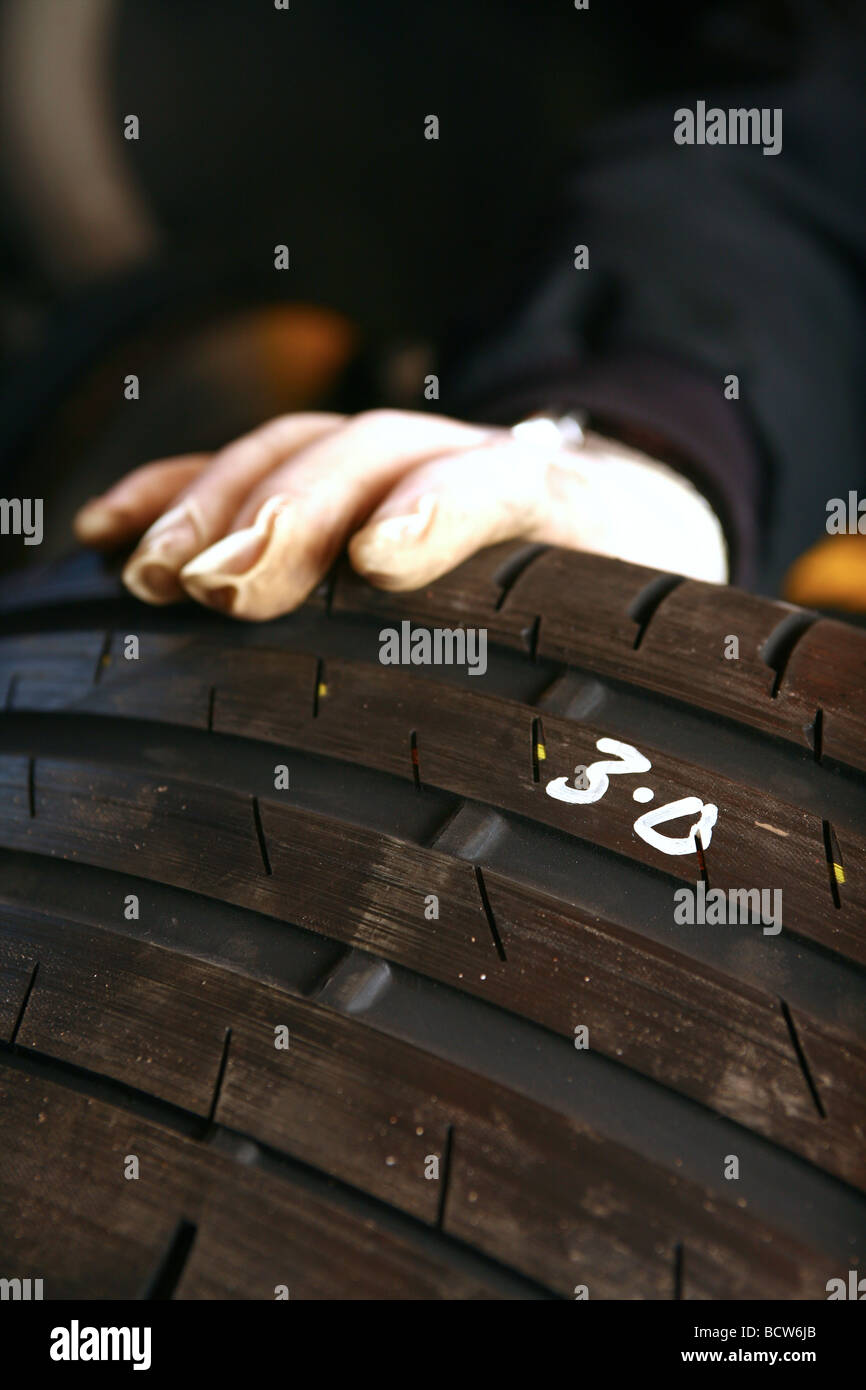 Close up of tyre held by mechanic - Stock Image
