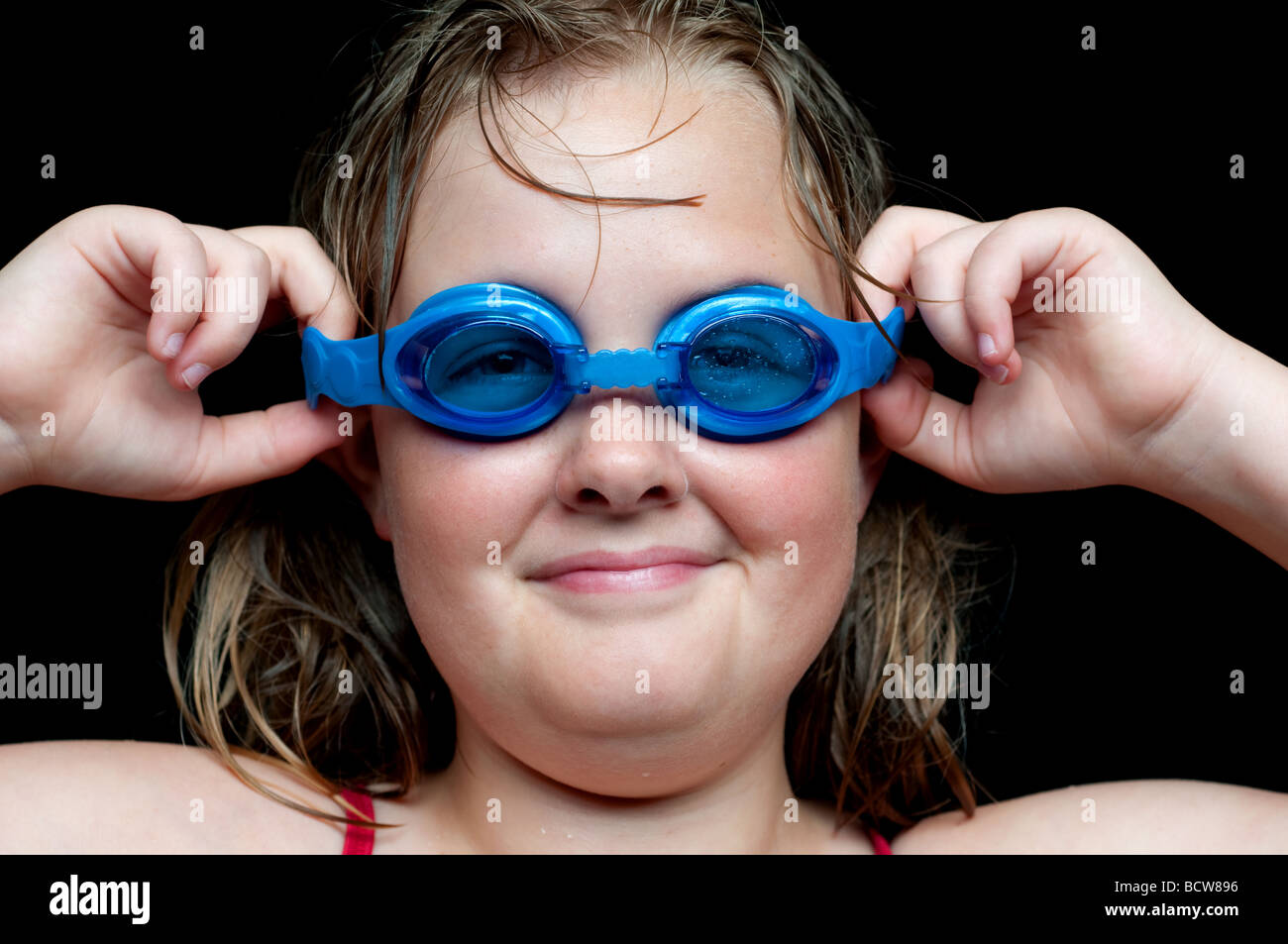 A horizontal image of a young girl adjusting her swimming goggles - Stock Image