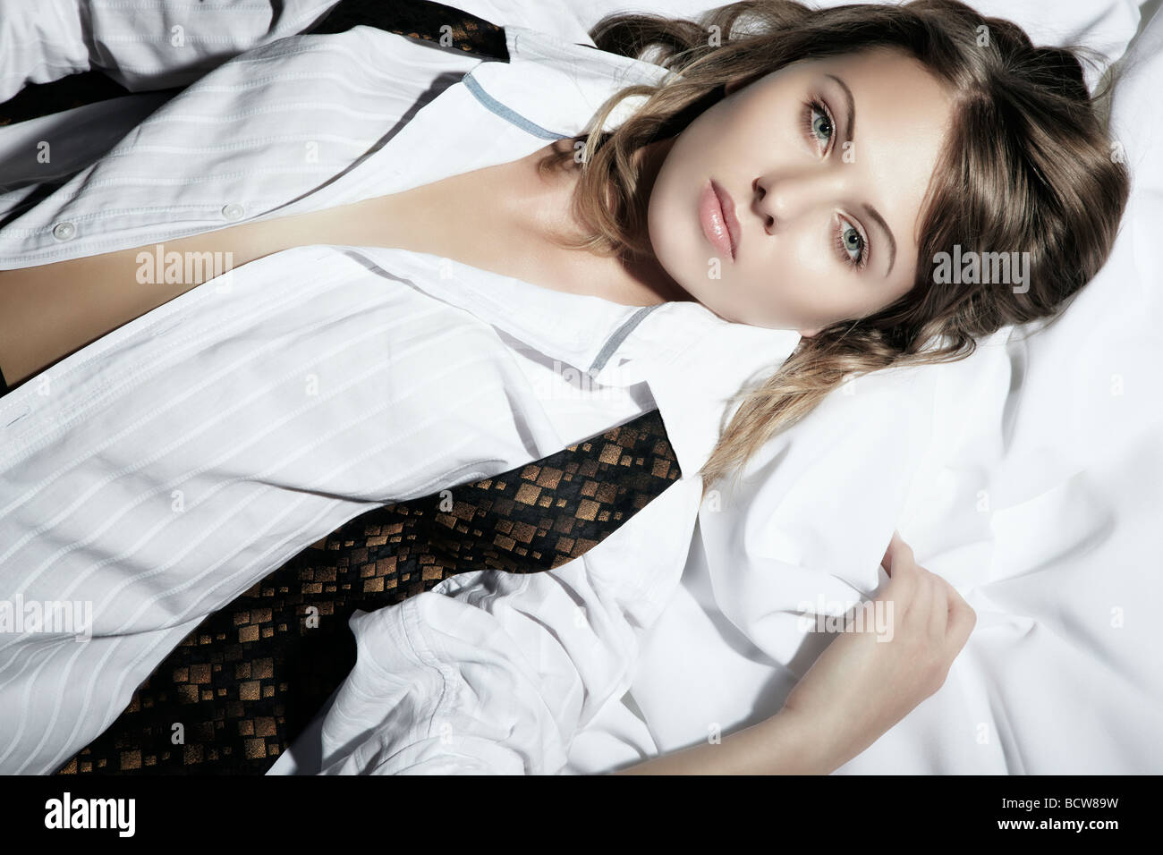 Portrait of a young woman, lying, dressed in a man's shirt and tie, looking at the viewer - Stock Image