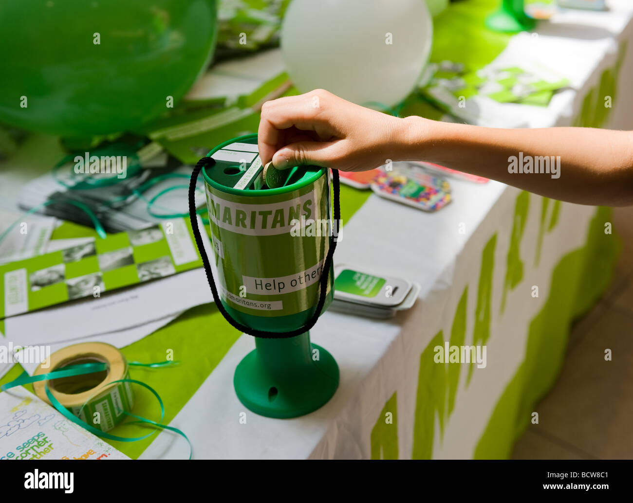 A person donating a pound coin to the Samaritans charity. - Stock Image