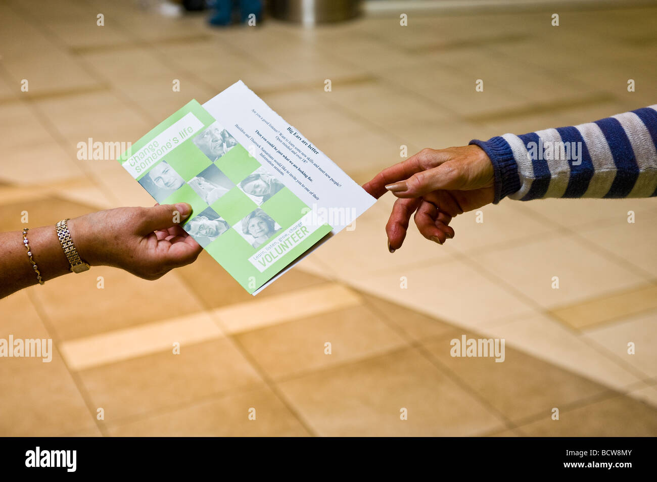 A volunteer from the charity Samaritans distributing leaflets. - Stock Image