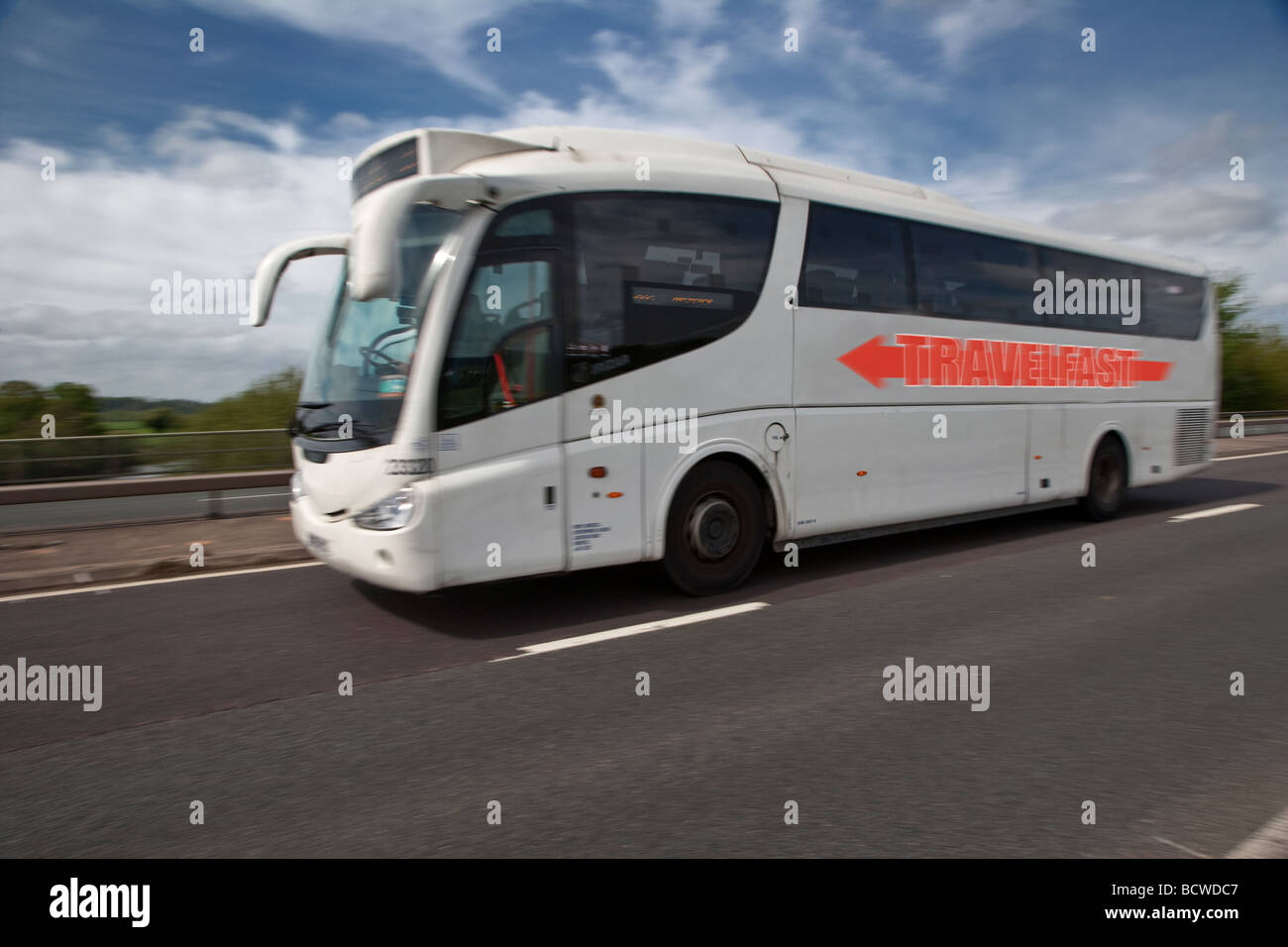 Modern coach bus (fictitious company) on road in summer. - Stock Image
