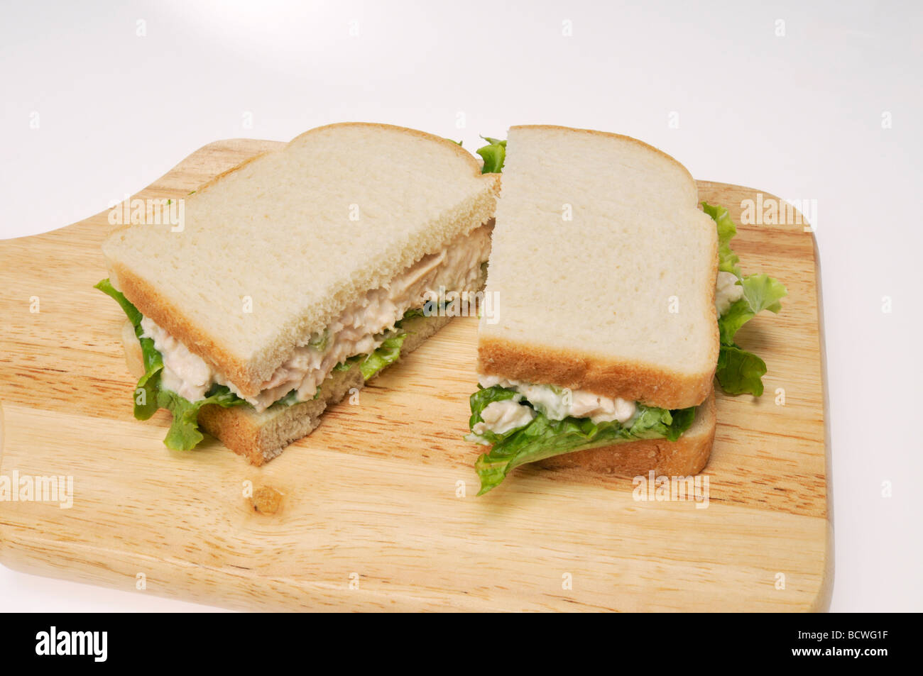 Tuna mayo sandwich on white bread with lettuce on  wood cutting board with white background. - Stock Image