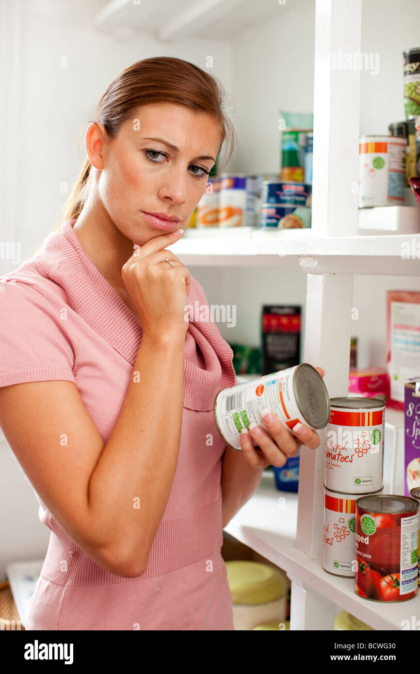 Woman looking at food label on back of tin - Stock Image