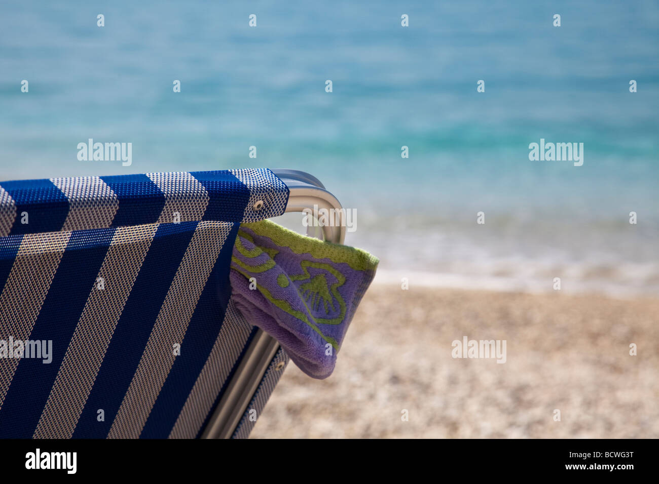 lazy days on a beach in Kefalonia, greek island in the sun, deck chair and umbrella at the ready, sand, blue sky - Stock Image