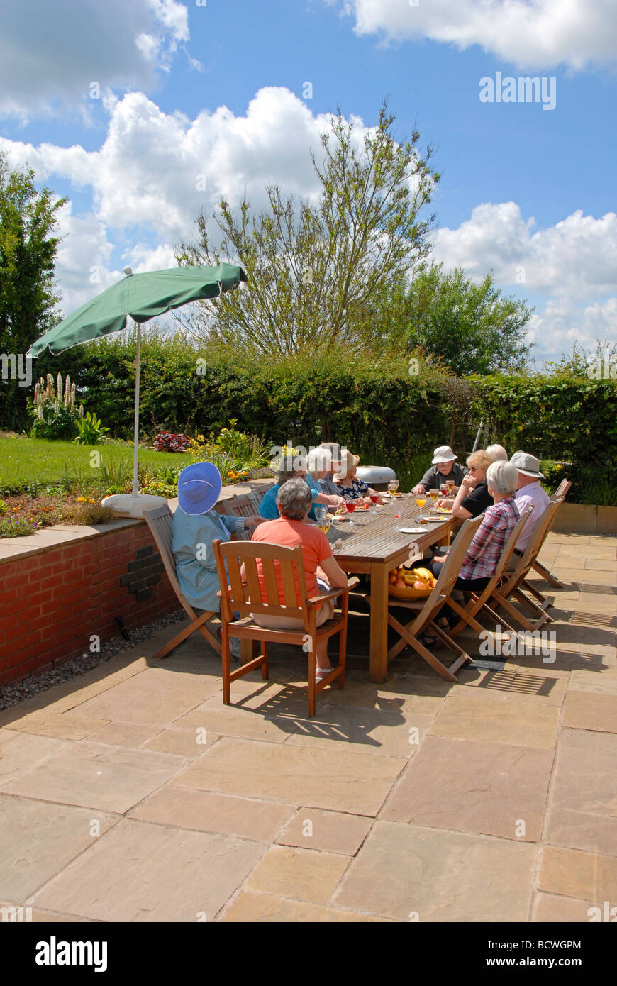 Group of elderly people enjoying a meal in the open air - Stock Image