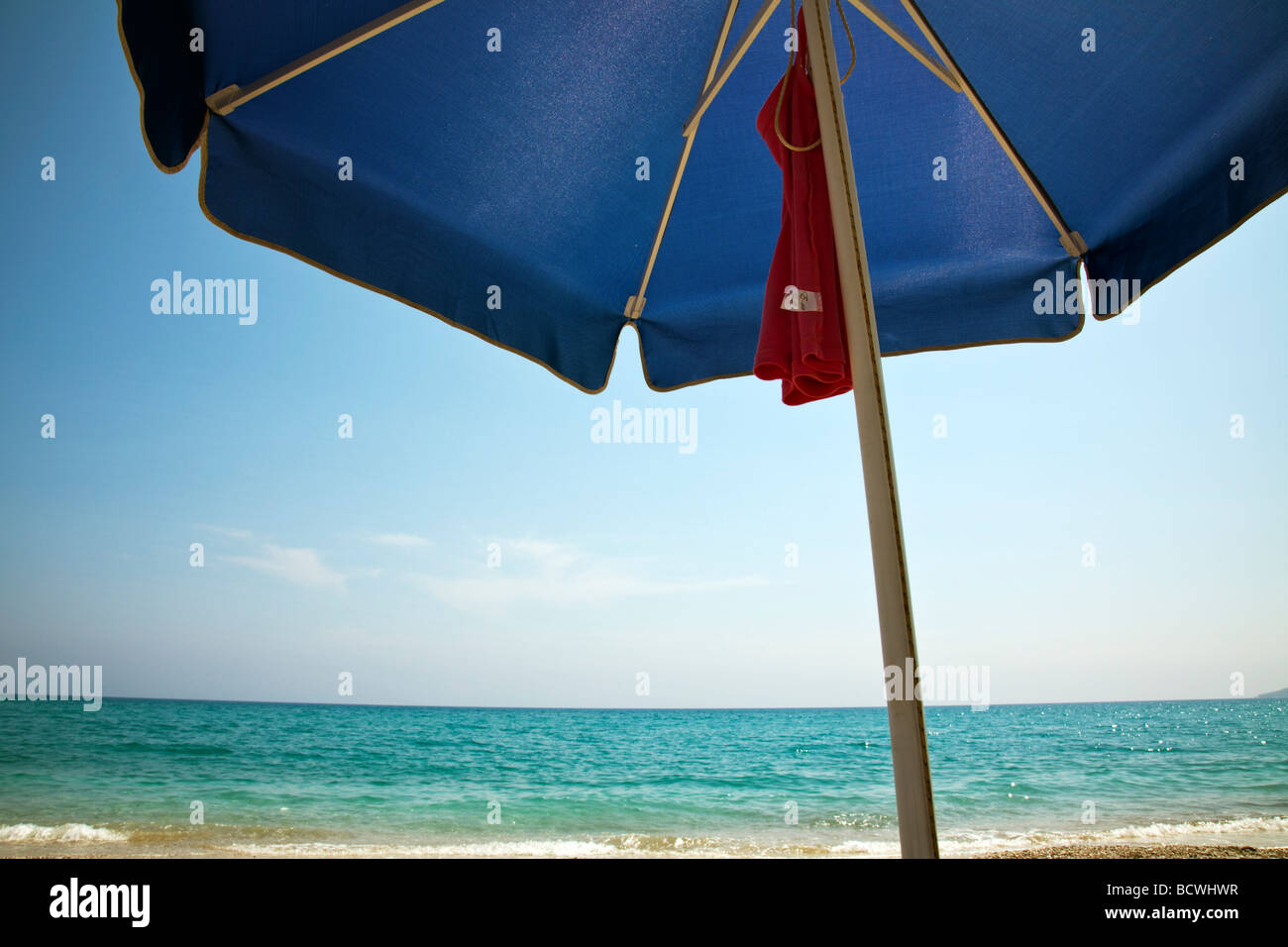 lazy days on a beach in Kefalonia, greek island in the sun, umbrella at the ready, sand, blue sky under parasol - Stock Image