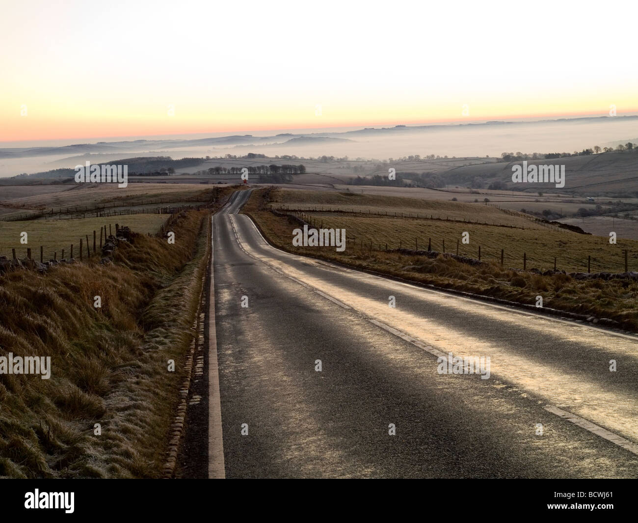 Sunrise over the long empty road to Longnor near Buxton in the Peak District, Derbyshire England UK - Stock Image