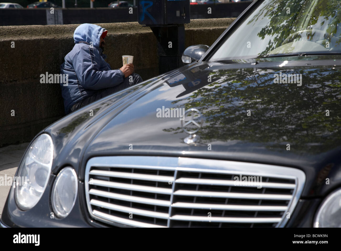 male man street beggar lying beside a parking ticket machine and mercedes car looking for spare change dublin city - Stock Image