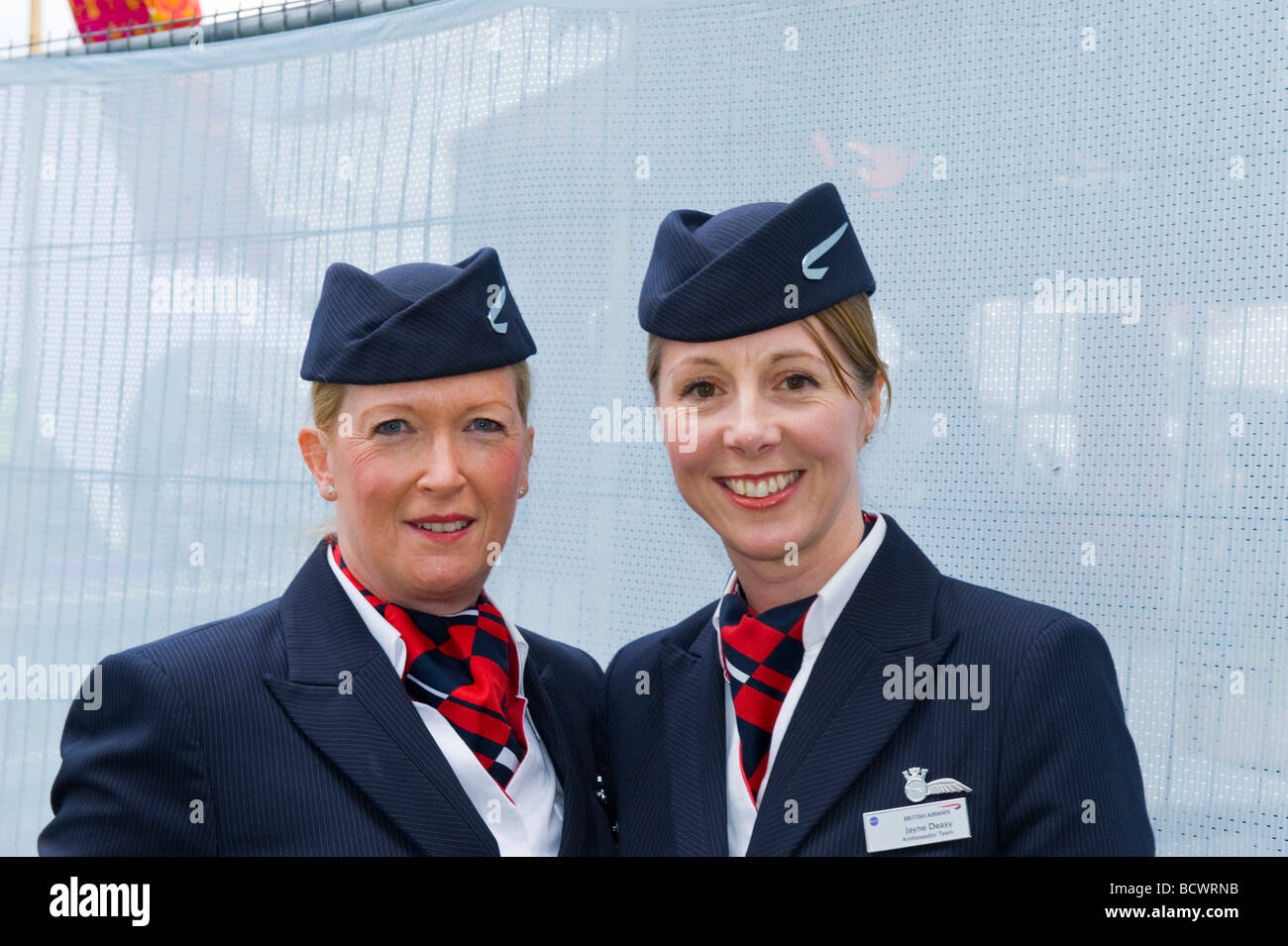Taste of London food fair sponsored by British Airways or BA , two pretty smiling air hostesses crew in uniform - Stock Image