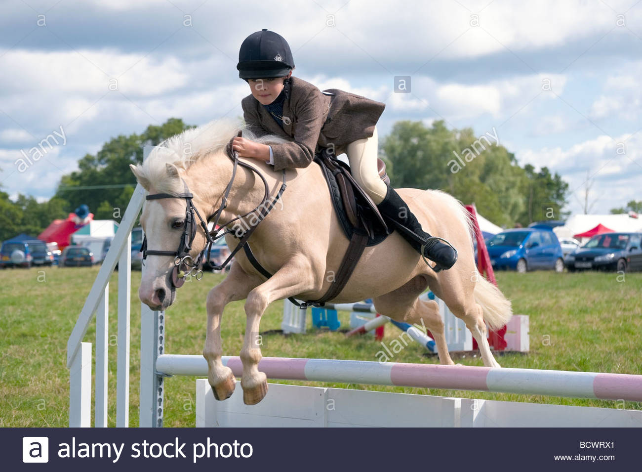 Beautiful palomino pony frozen in mid-air as it leaps over a show jumping fence at Pembridge Show. Young girl riding. - Stock Image