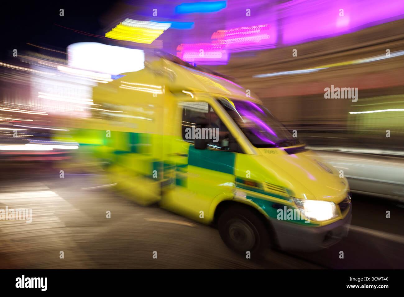 An ambulance races along a London street at night. - Stock Image