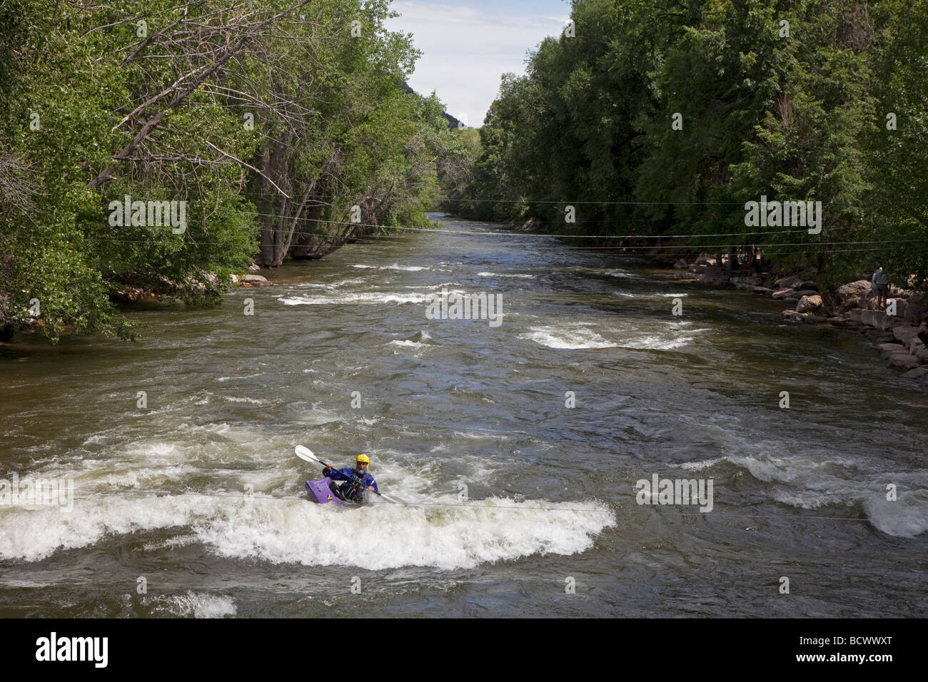 A man practices his kayaking technique in rapids on the Arkansas River in Salida, Colorado - Stock Image