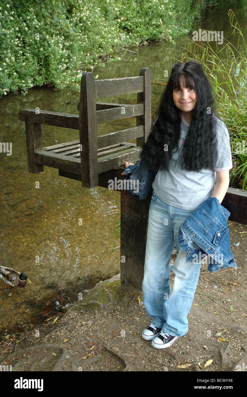 young woman standing next to a ducking stool at Christchurch, Dorset, England, UK - Stock Image