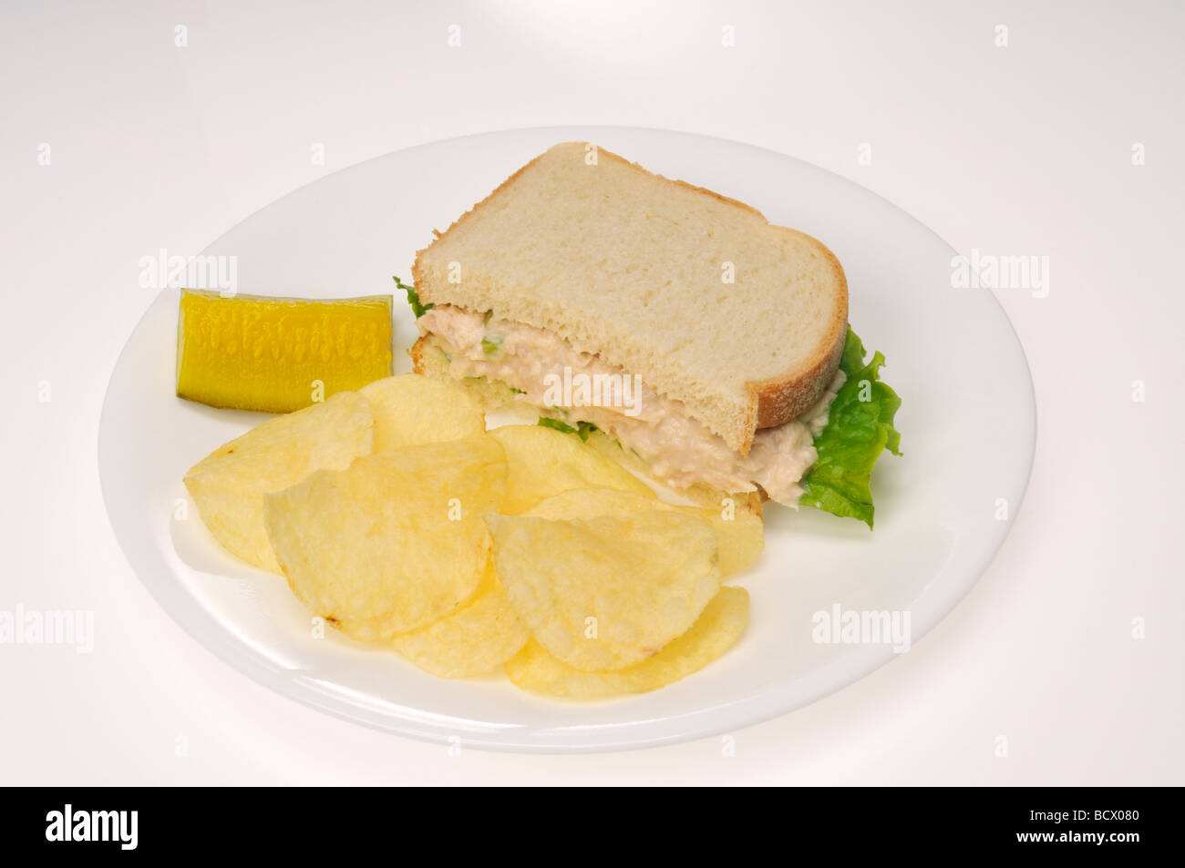 Tuna mayo sandwich with lettuce on white bread with pickle and potato chips - Stock Image