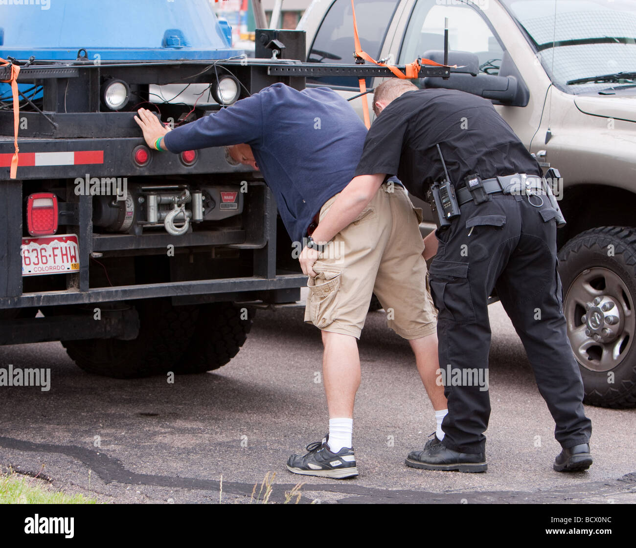 A fake arrest a real Salina Kansas police officer pretends to frisk a man. - Stock Image