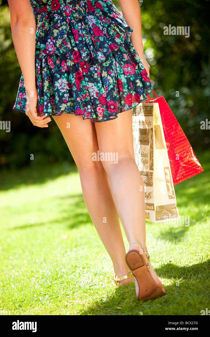 Close up of wmans legs and shopping bags - Stock Image