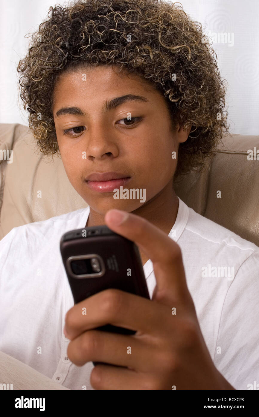 teenage boy of mixed race reading text on his mobile phone - Stock Image