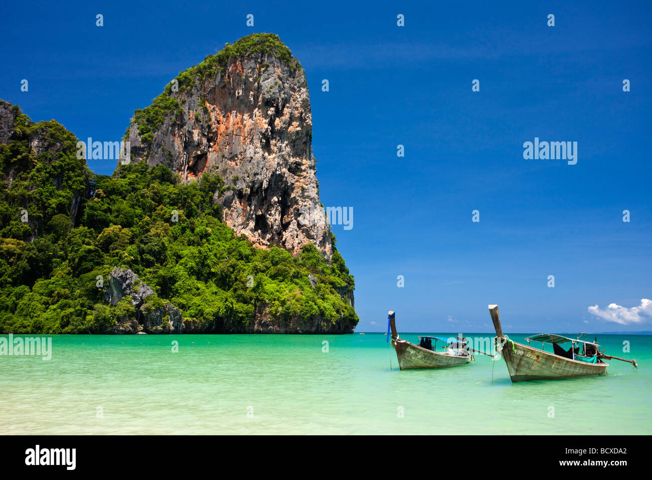 Longtail boats lined up on Railay Beach, Thailand - Stock Image