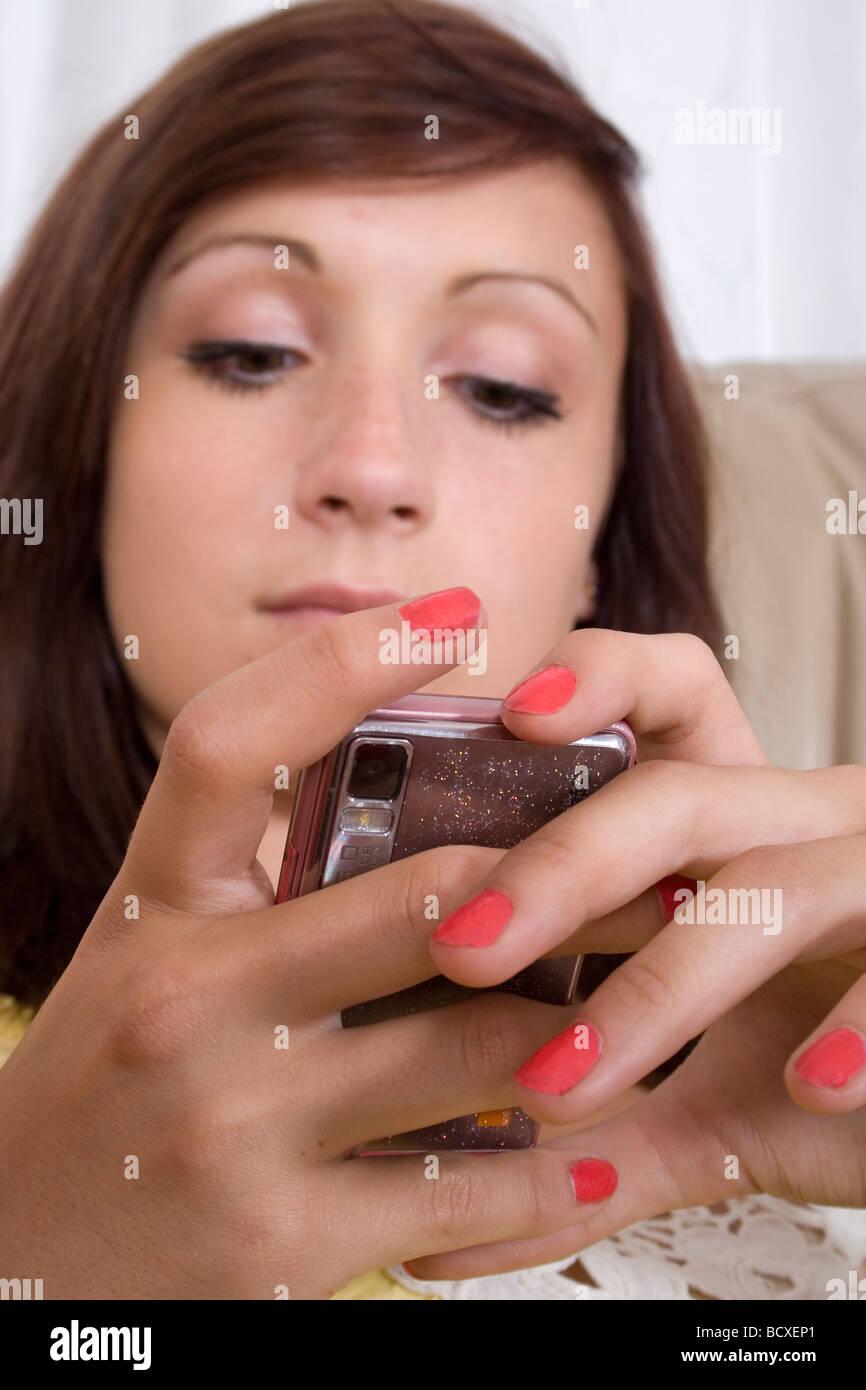 teenage girl texting on her mobile phone - Stock Image