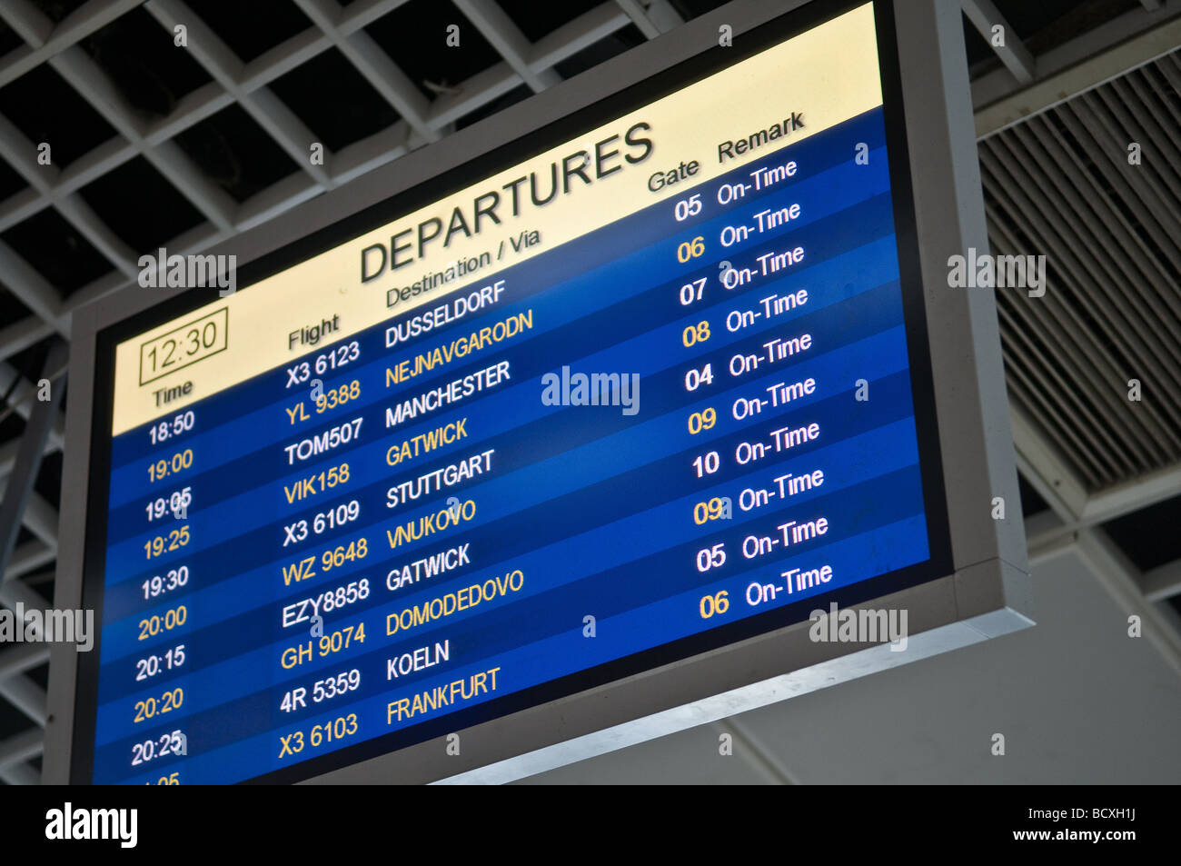 Flight departure information board at airport - Stock Image