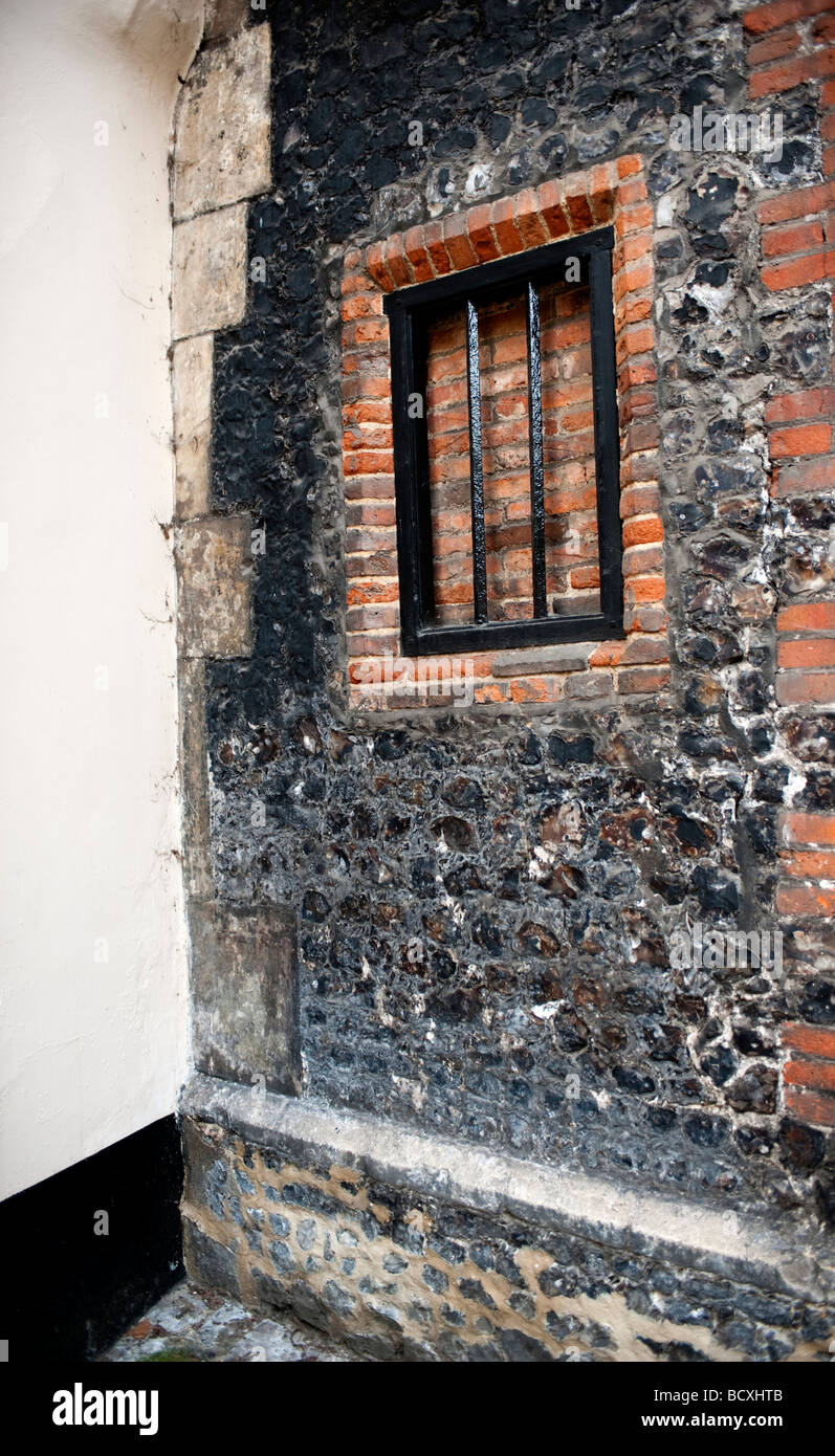 Old window with bars set into a brick & stone wall. - Stock Image