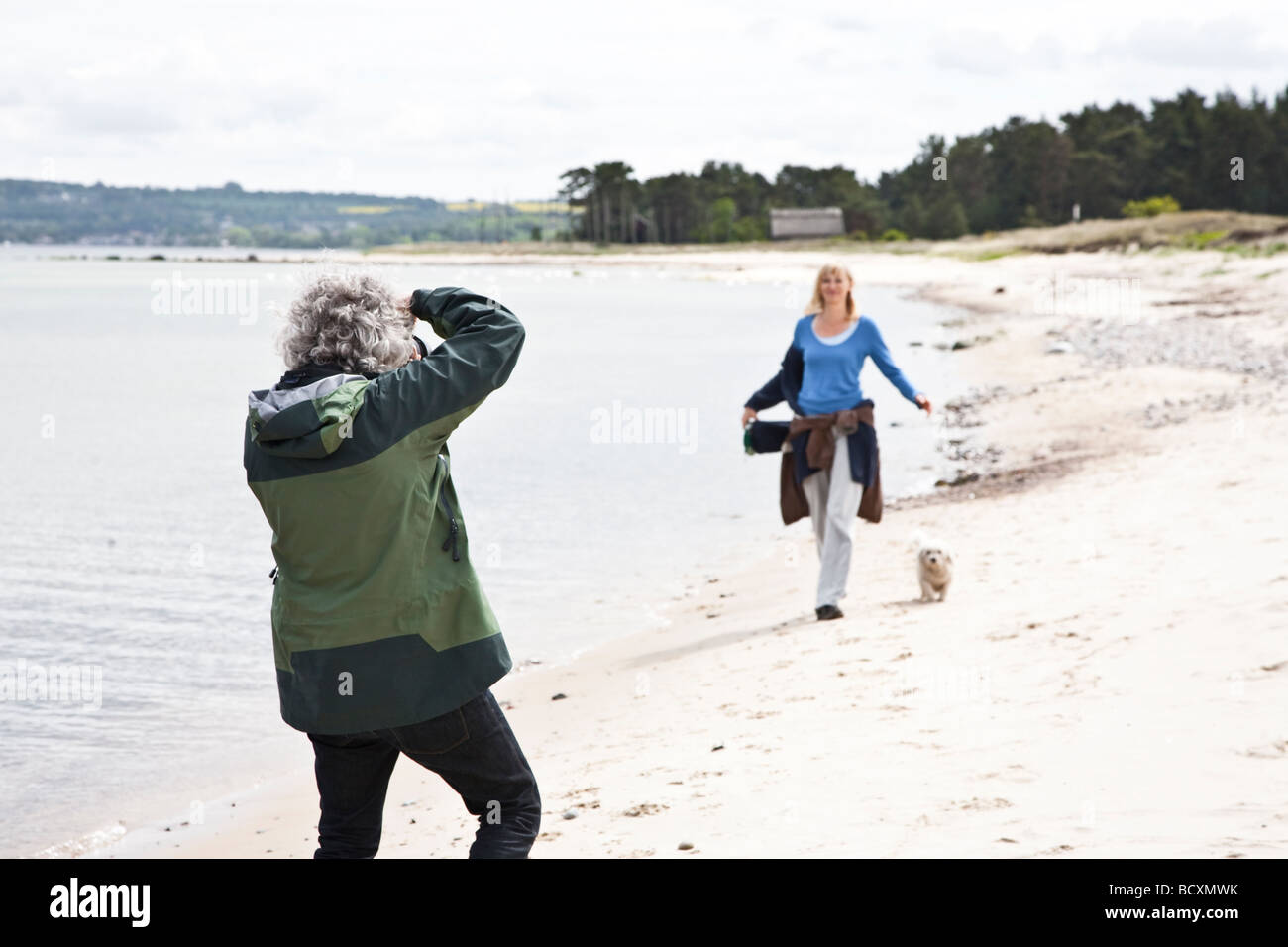 Model being photographed on the beach Focus is on photographer - Stock Image
