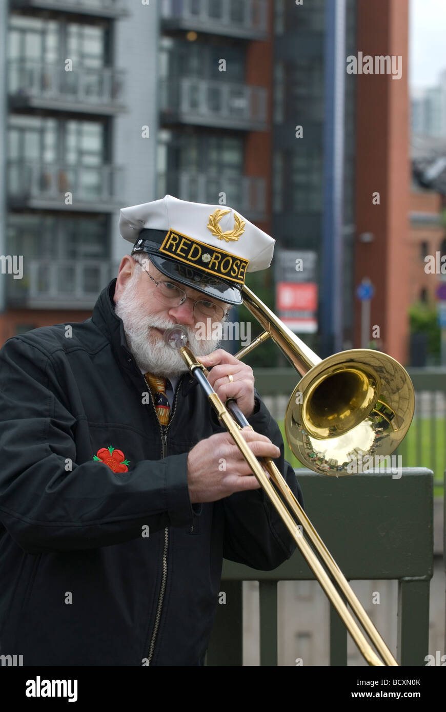 Red rose band member playing the trombone outdoors in Manchester UK - Stock Image