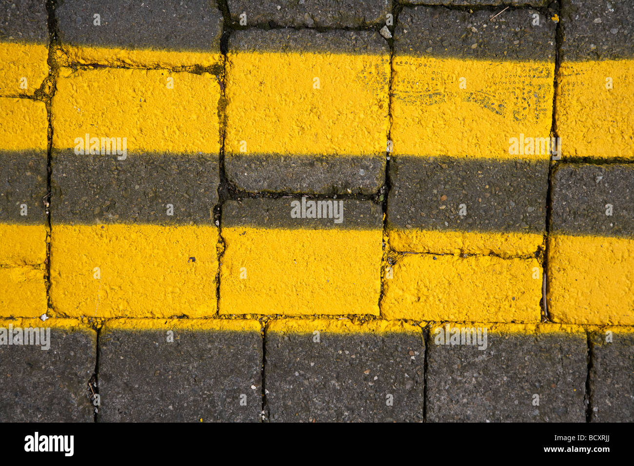 freshly painted double yellow lines on a cobblestone street in dublin republic of ireland - Stock Image