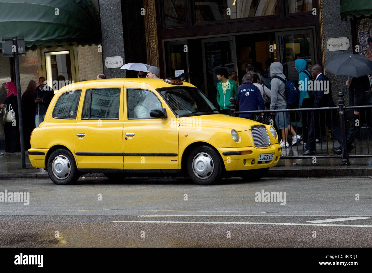 Yellow Taxi outside Harrods - Stock Image