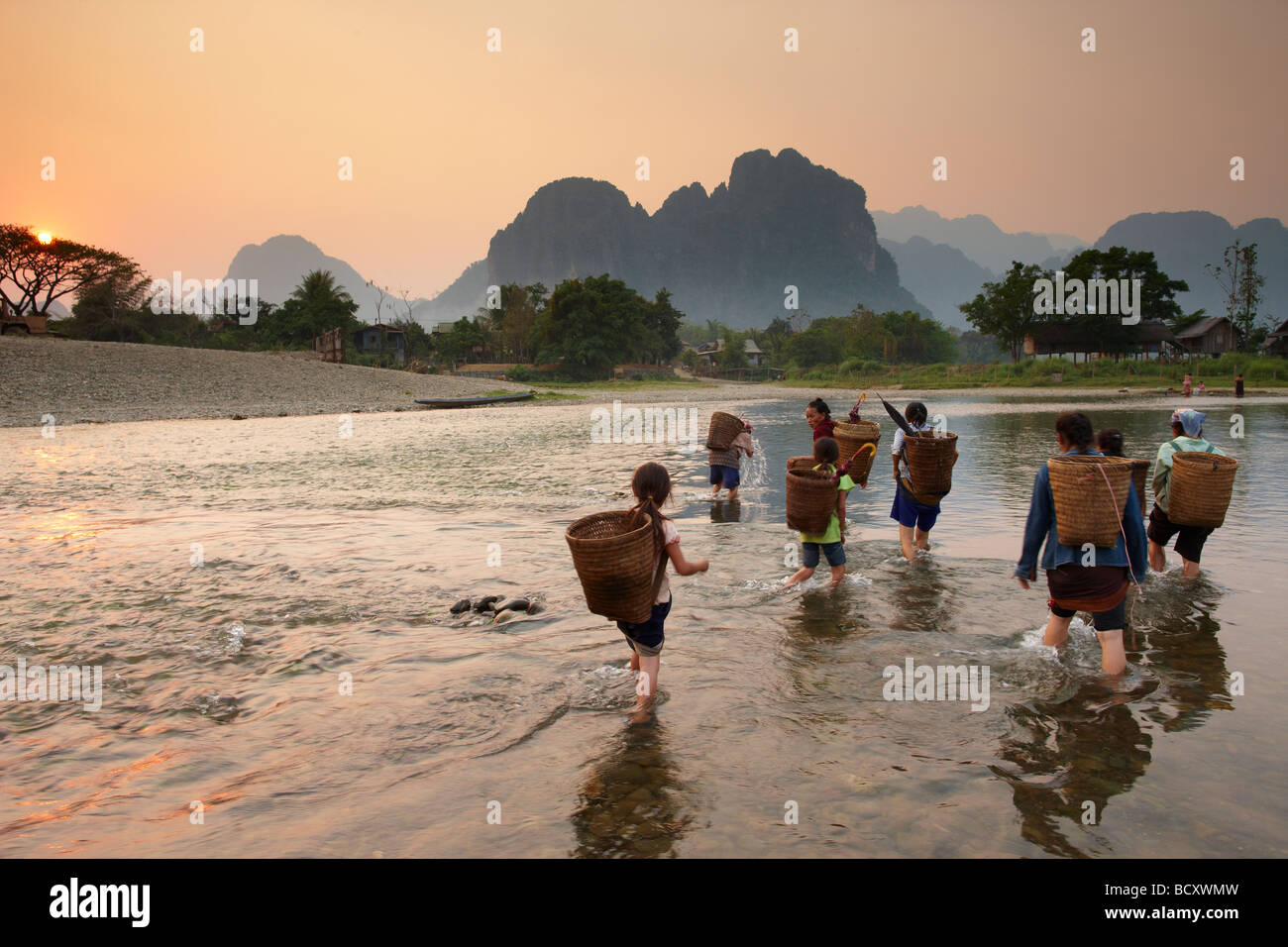 women and girls fording the Nam Song River at Vang Vieng, Laos - Stock Image