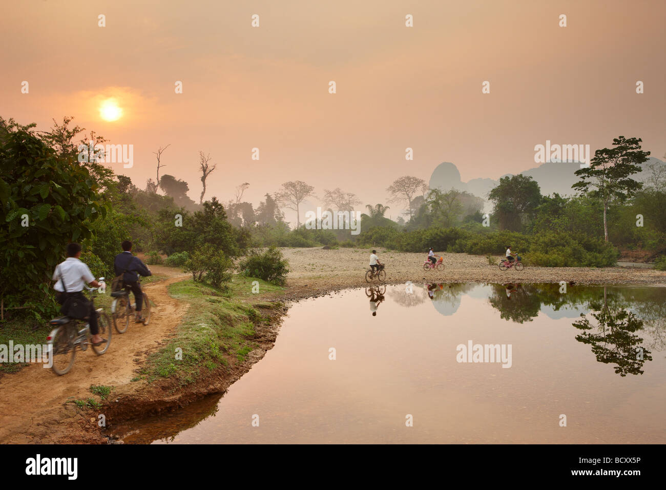 children cycling to school at dawn; rush hour in the countryside near Vang Vieng, Laos - Stock Image