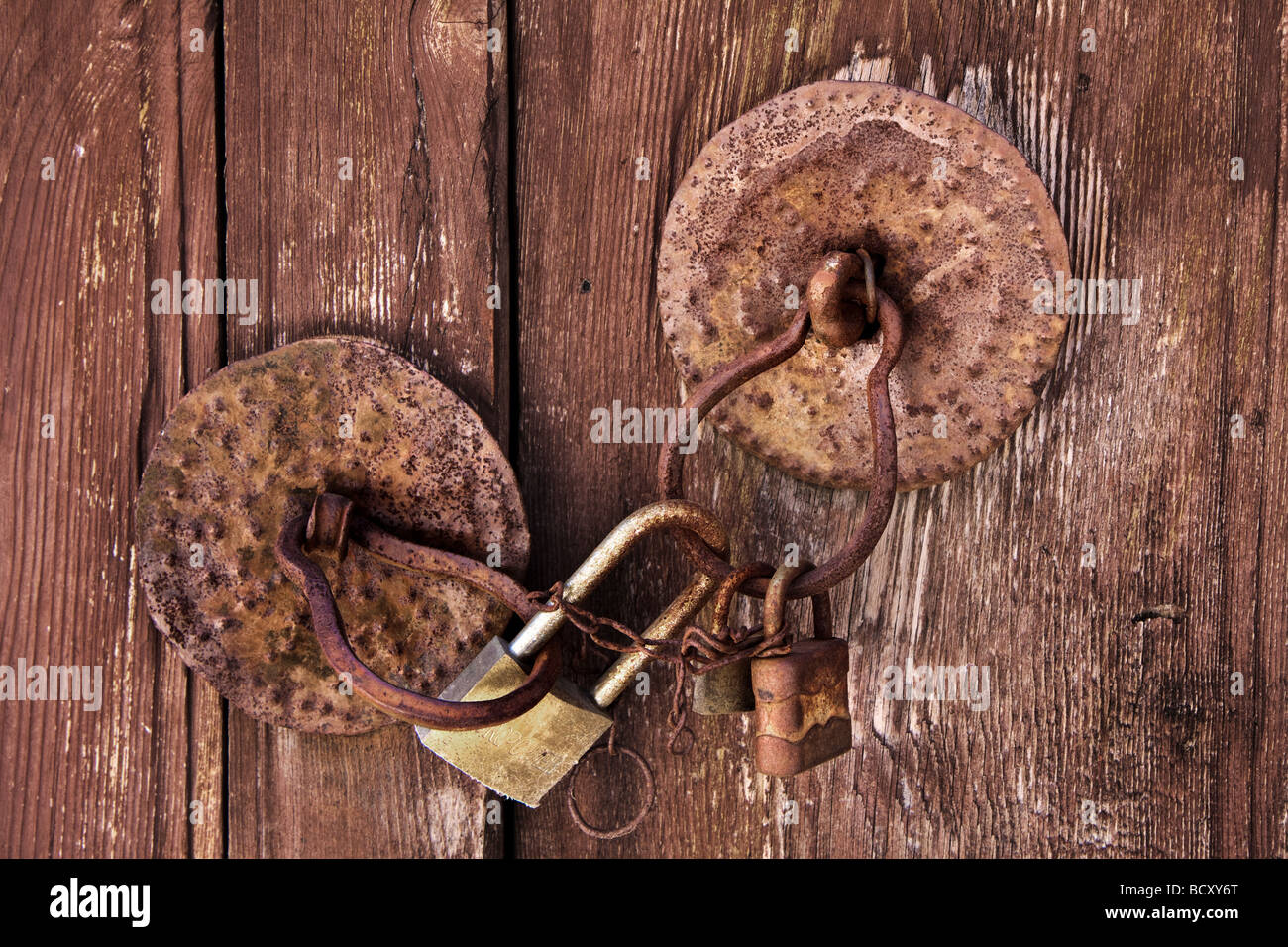 Old wooden door with circular handles and three padlocks - Stock Image