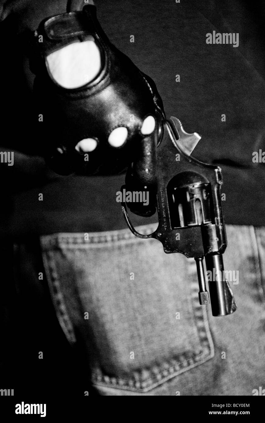 Assailant pulling out a gun - Stock Image