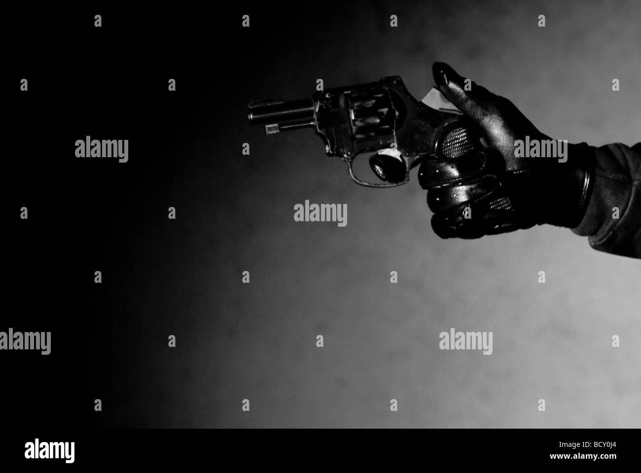 Assailant holding a gun - Stock Image