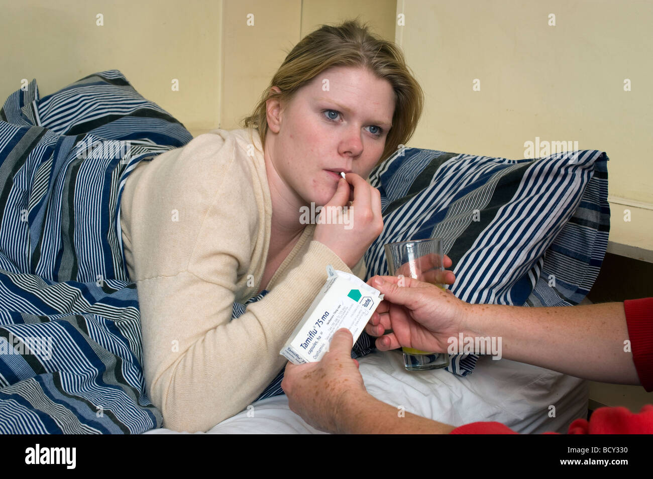 Young woman with Swine Flu lying in bed being given a Tamiflu Tablet - Stock Image