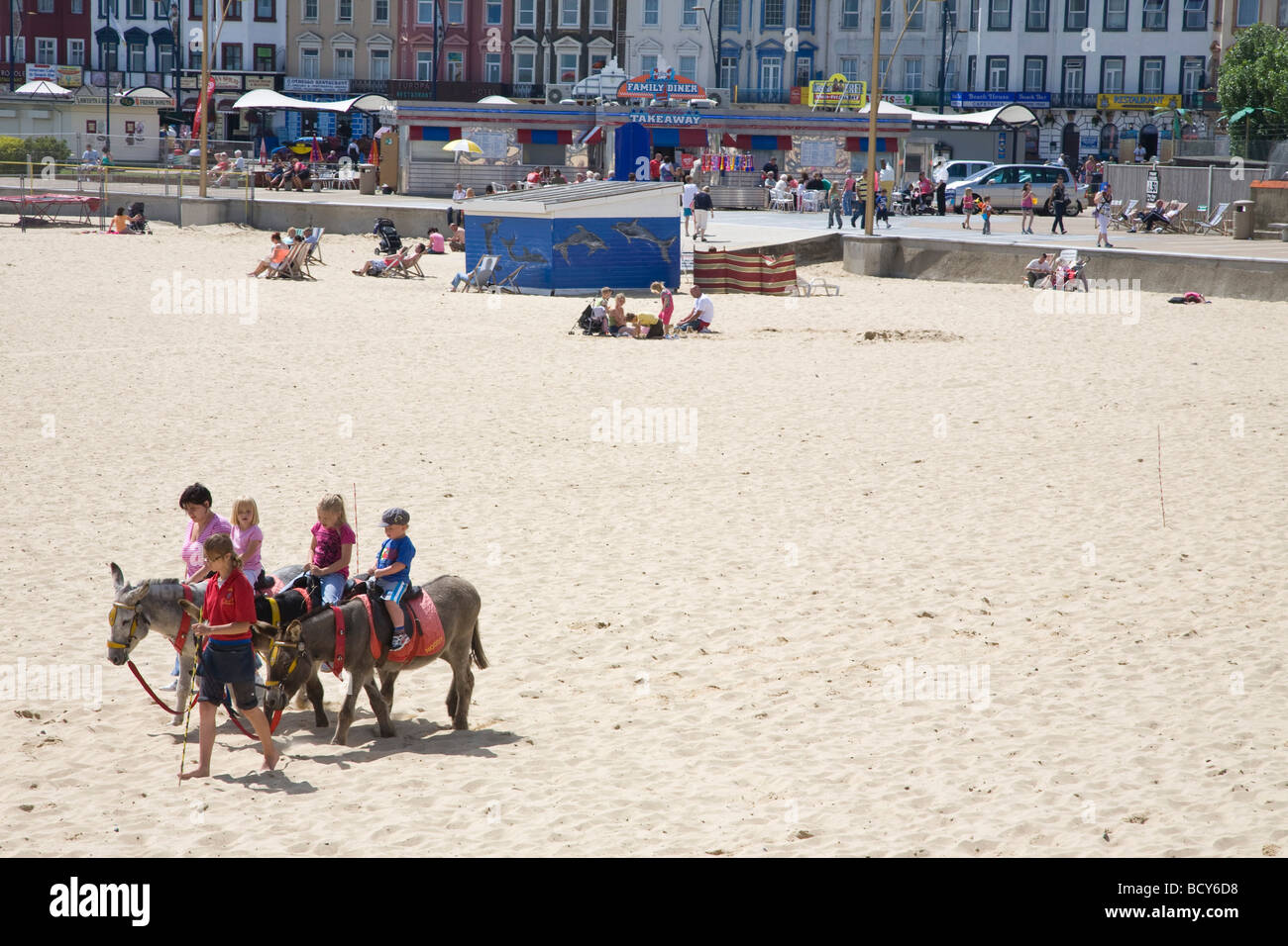 Children ride on the donkeys on Great Yarmouth's sandy beach Stock Photo