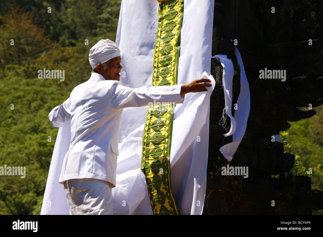 Priest decorating a deity's throne, Pura Pasaran Agung, at the volcano, Mount Agung, 2567m, Bali, Republic of - Stock Image