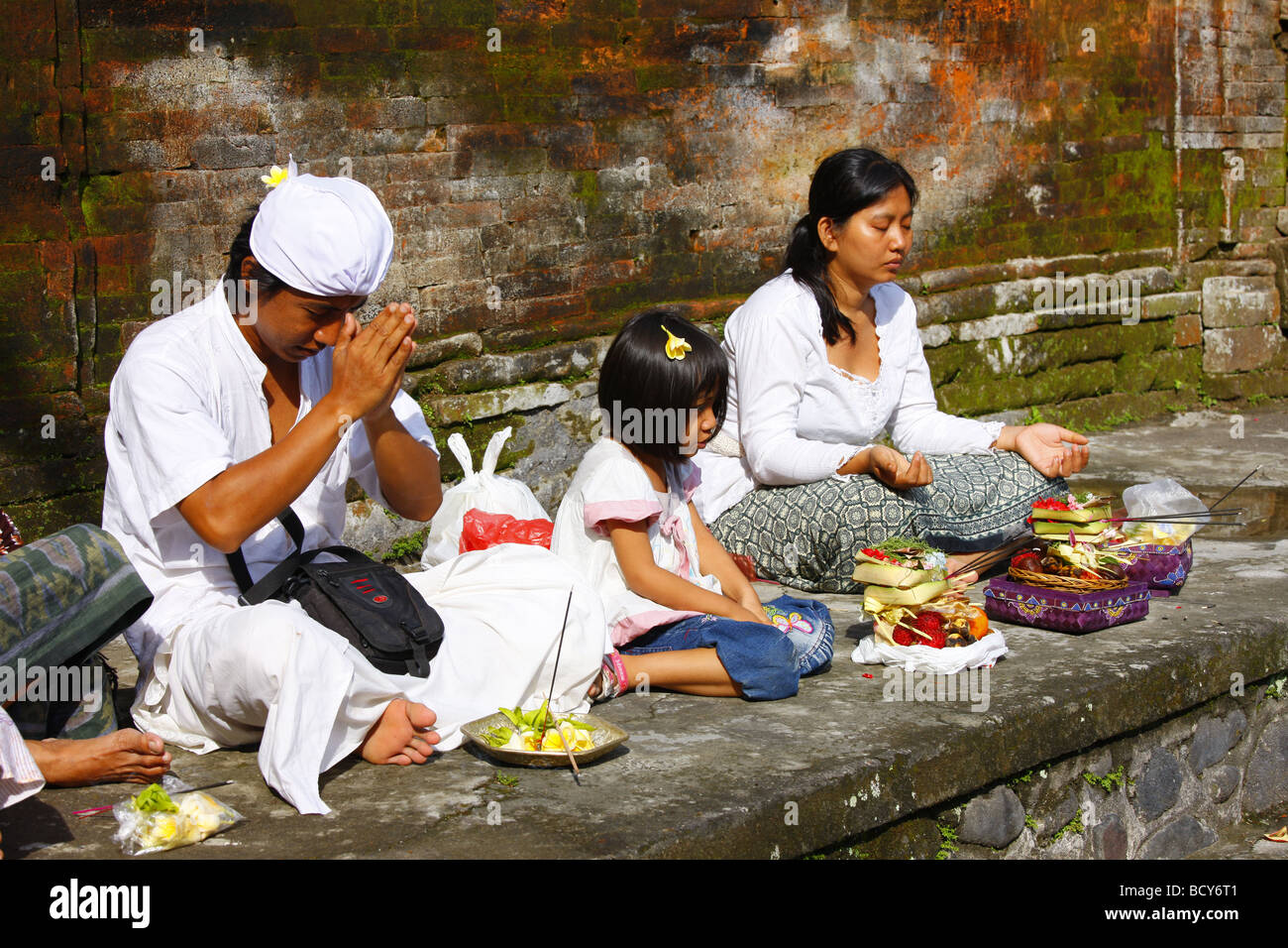 People at a ceremony at a sacred spring, Tirta Empul at Tampak Siring in the morning light, Bali, Republic of Indonesia, - Stock Image