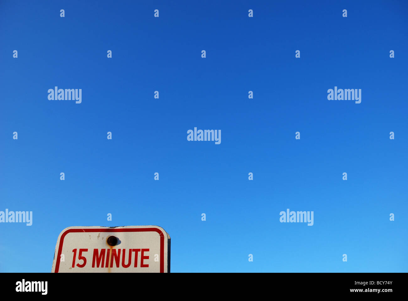 15 Minute parking sign against blue sky - Stock Image